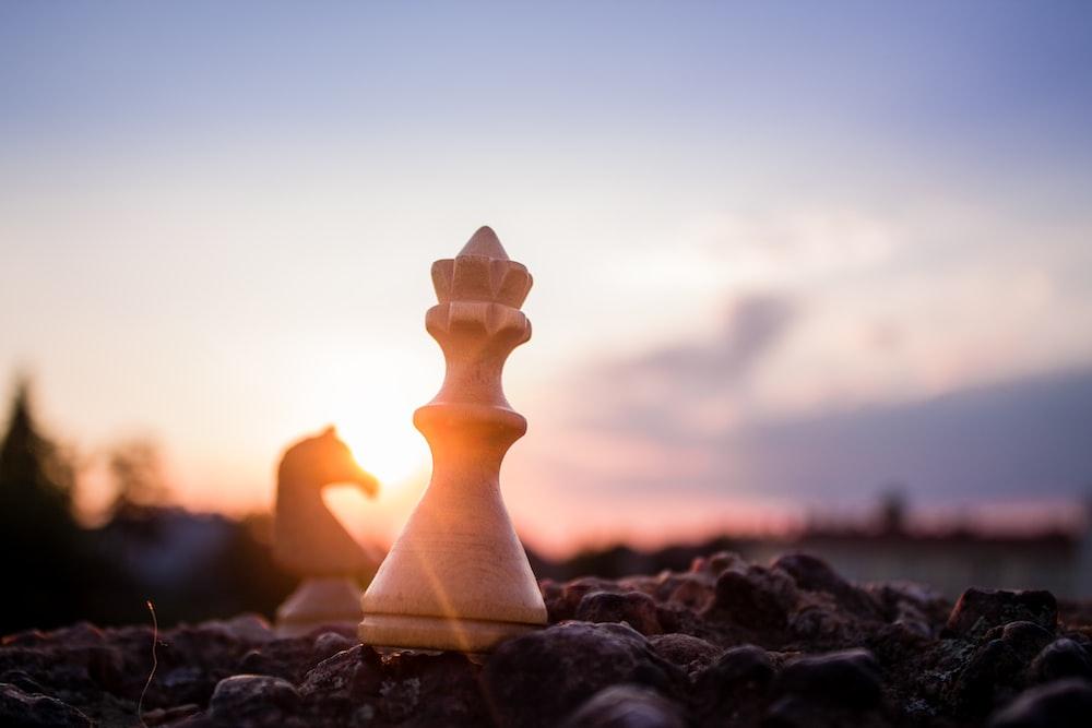 bishop chess piece on black rock at daytime