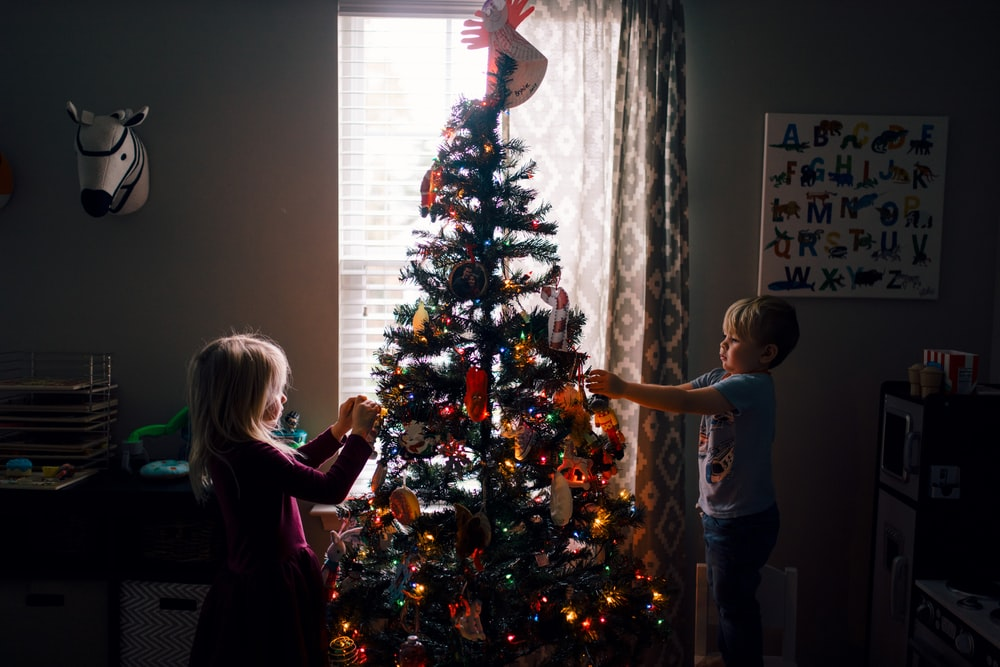 girl and boy standing near Christmas tree