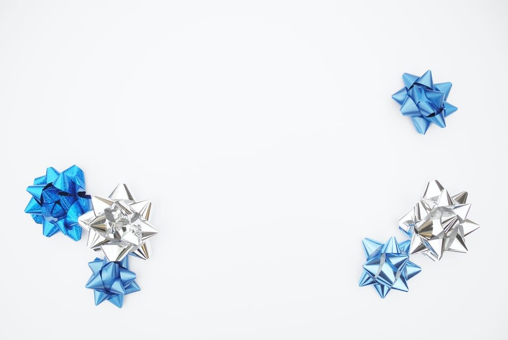 blue and silver gift box bows on white surface