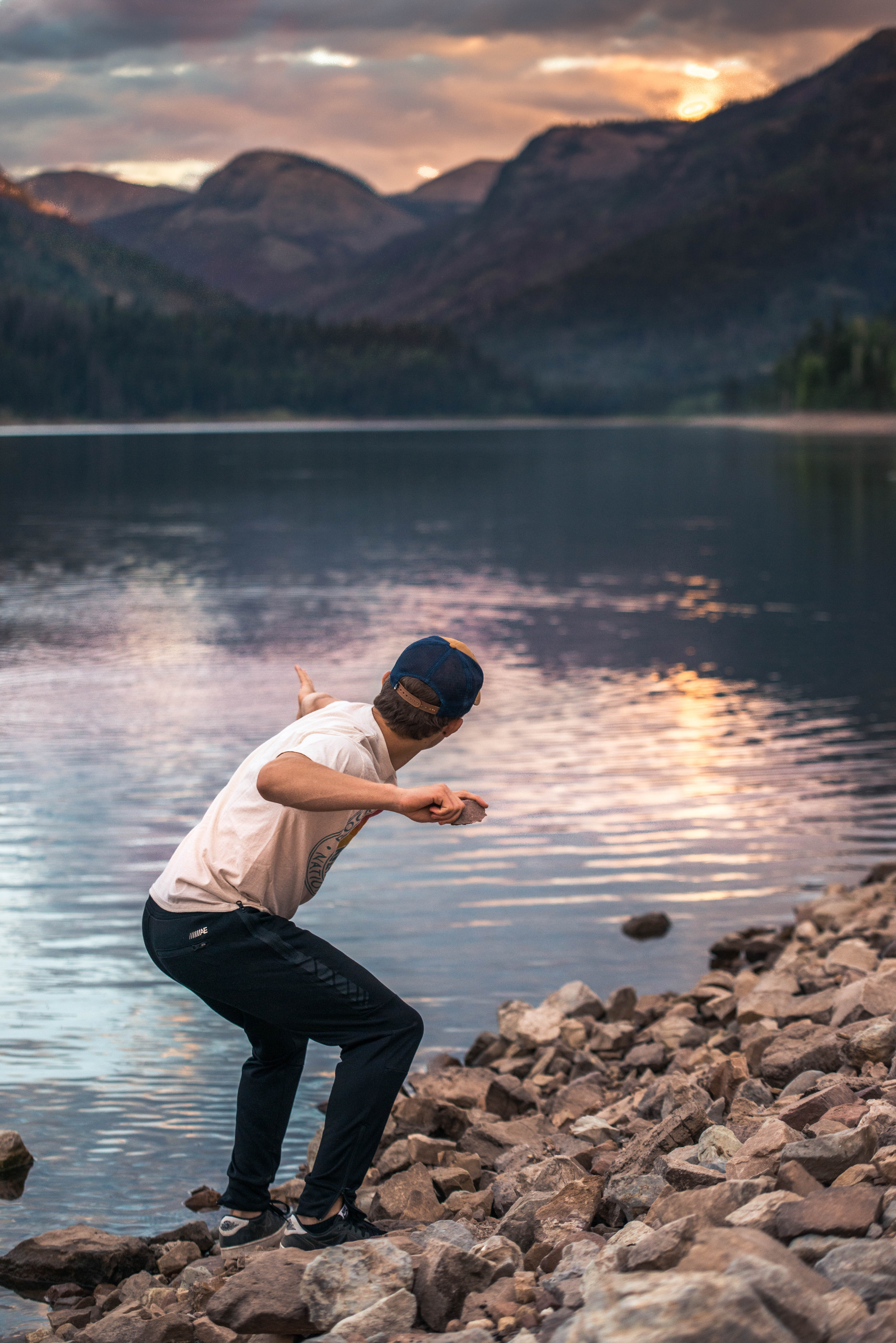 man holding stone near body of water during golden hour