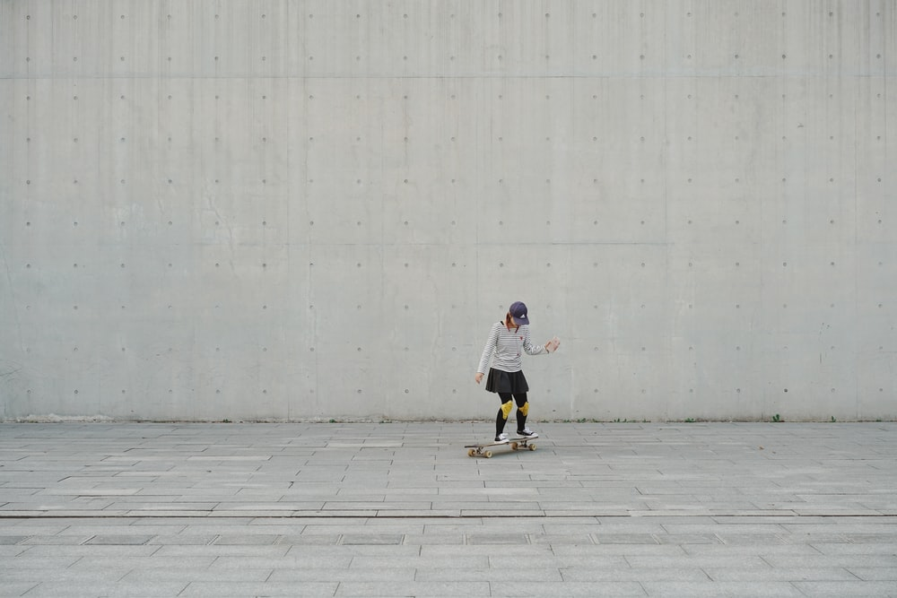 woman riding on skateboard during daytime