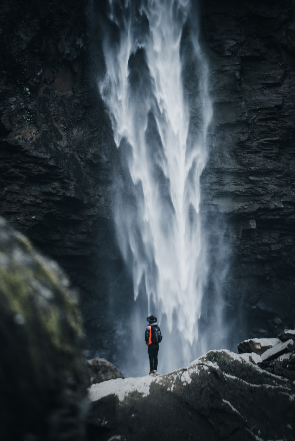 man standing near waterfalls