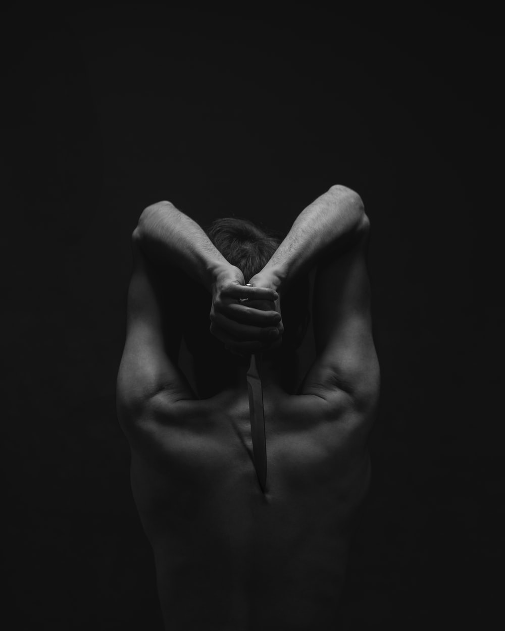 grayscale photography of person holding knife