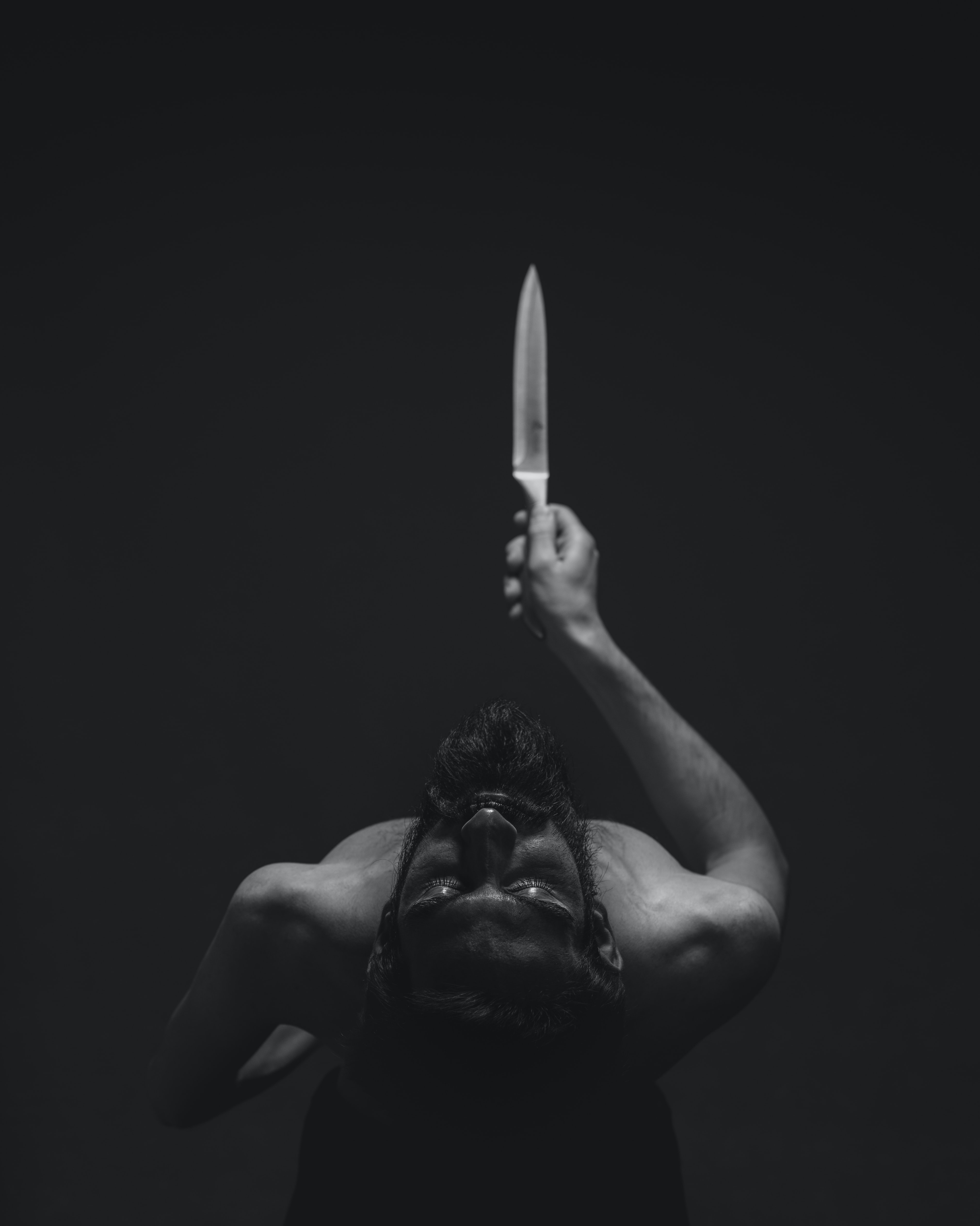 grayscale photography of man holding knife