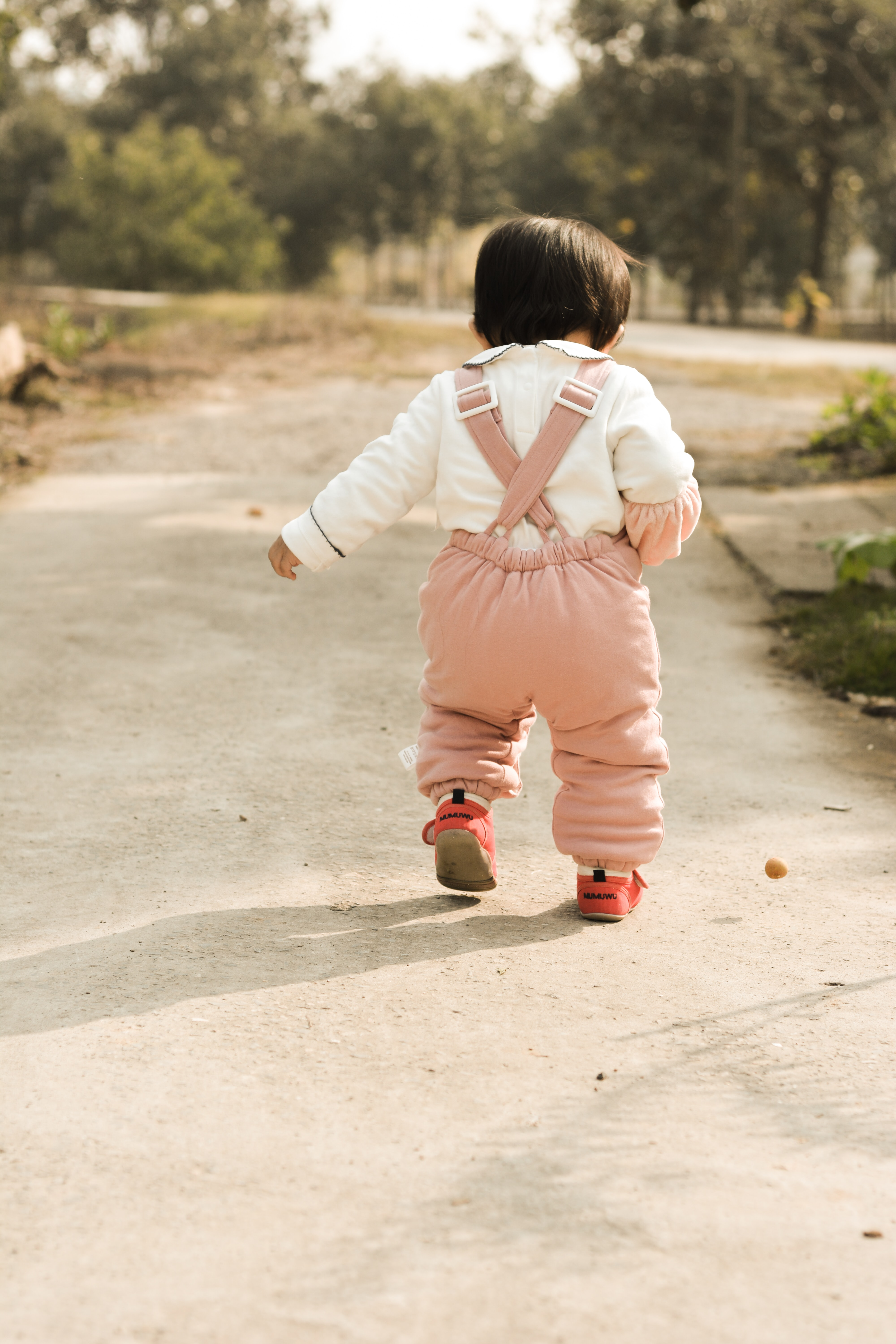 toddler walking on pathway during daytime