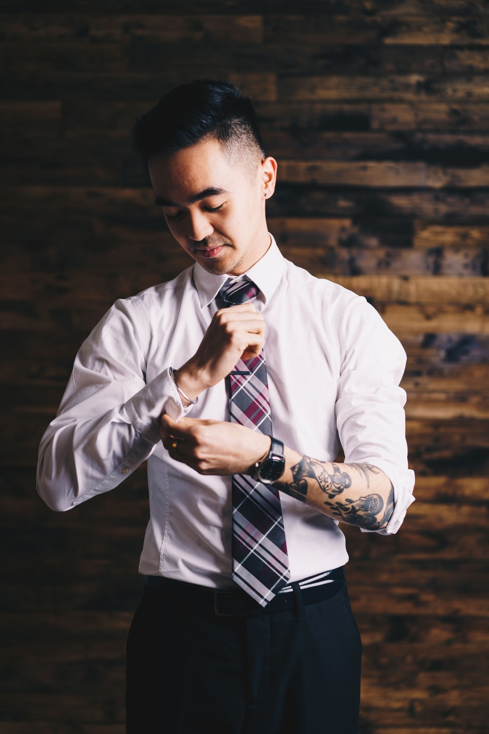 man holding his sleeve and necktie