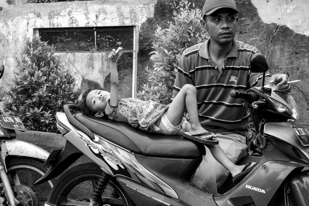 grayscale photography of boy on motorcycle