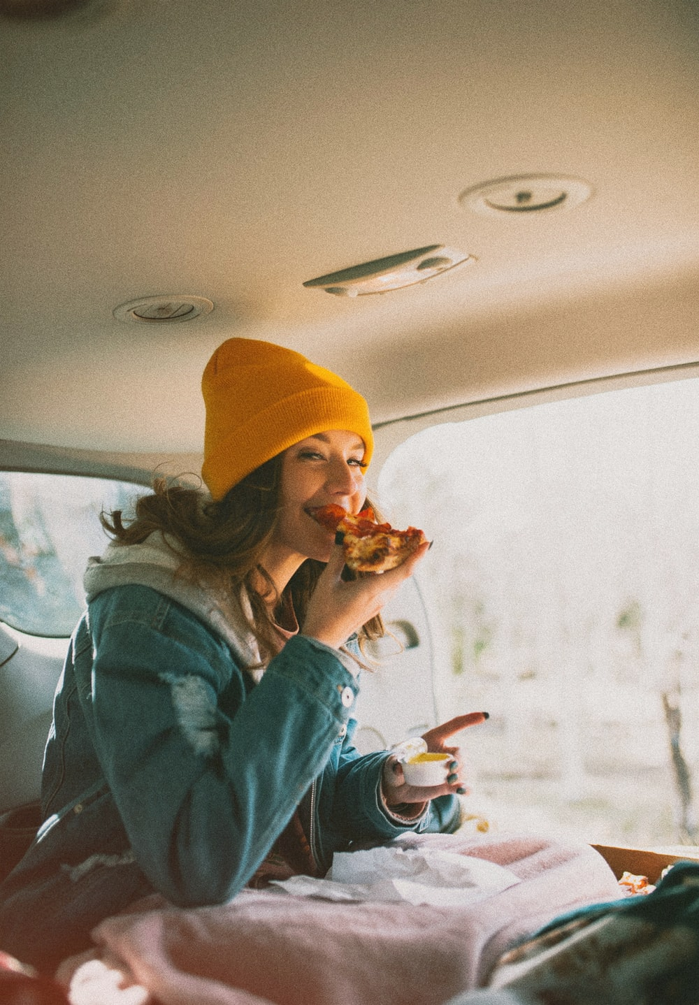 woman eating pizza inside vehicle