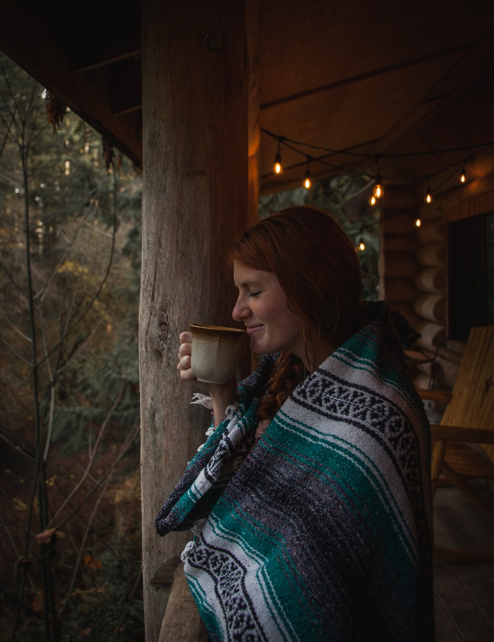 woman covering blanket standing and holding and smelling coffee