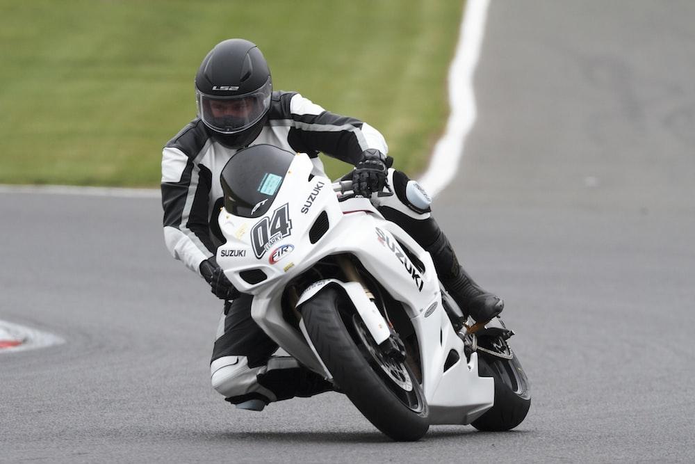 man riding white and black Suzuki sportbike