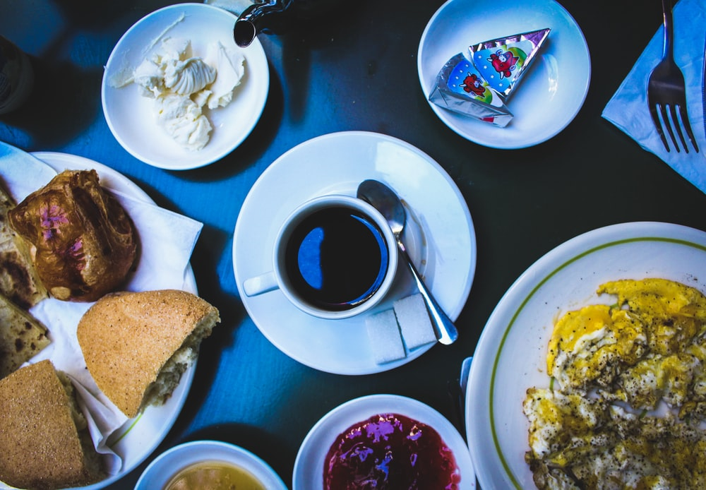 cooked foods on plate and black coffee