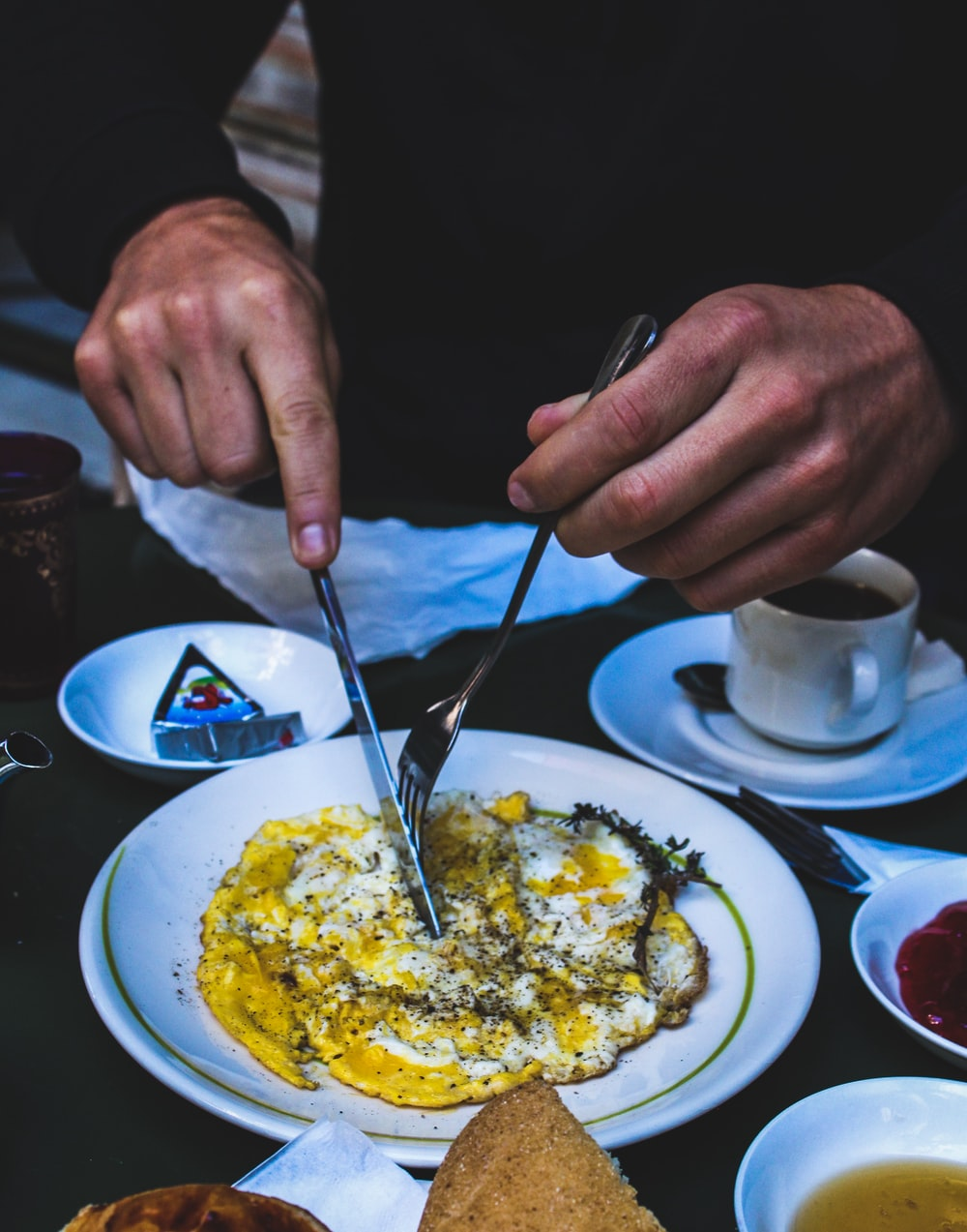 person holding butter knife and fork over cooked egg