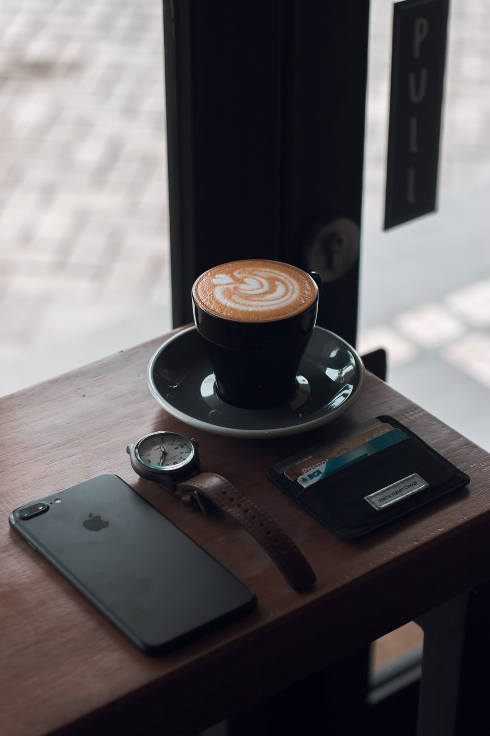 black ceramic teacup with coffee latte on saucer beside black iPhone 7 Plus on brown wooden table