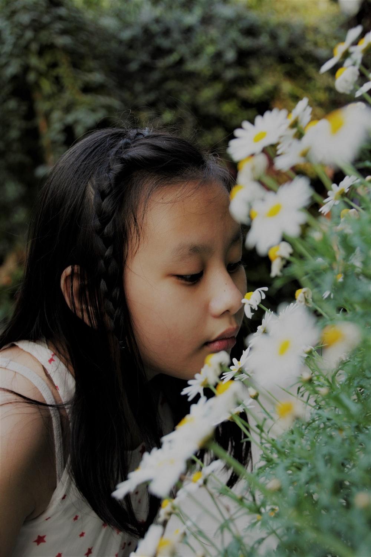 girl smelling white flower during daytime