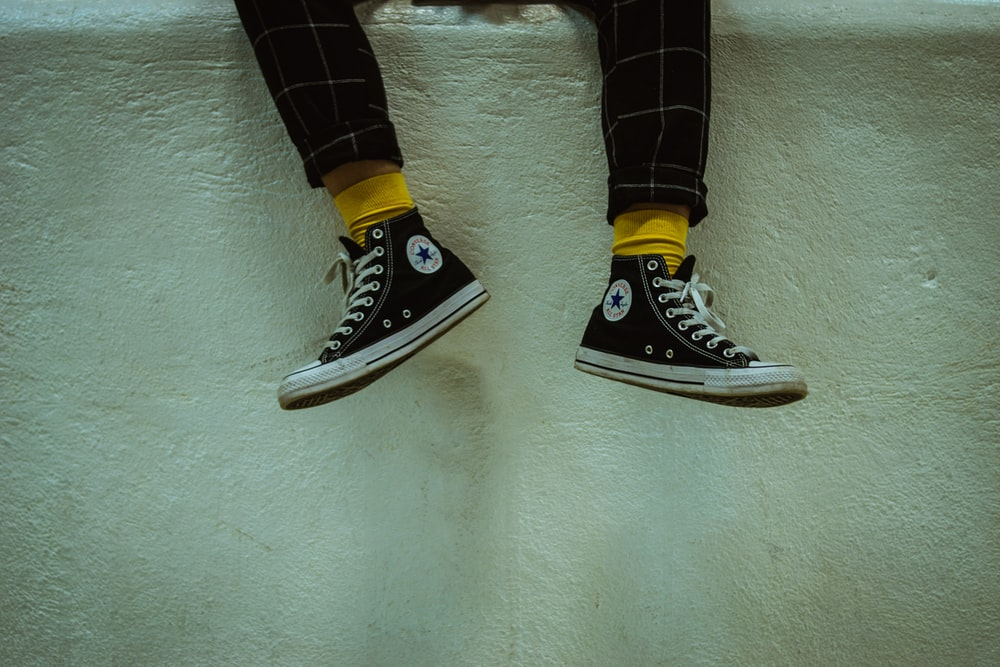 person wearing white-and-black Converse high-top sneakers