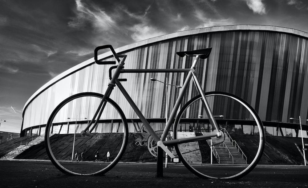 grayscale photography of road bike near stadium