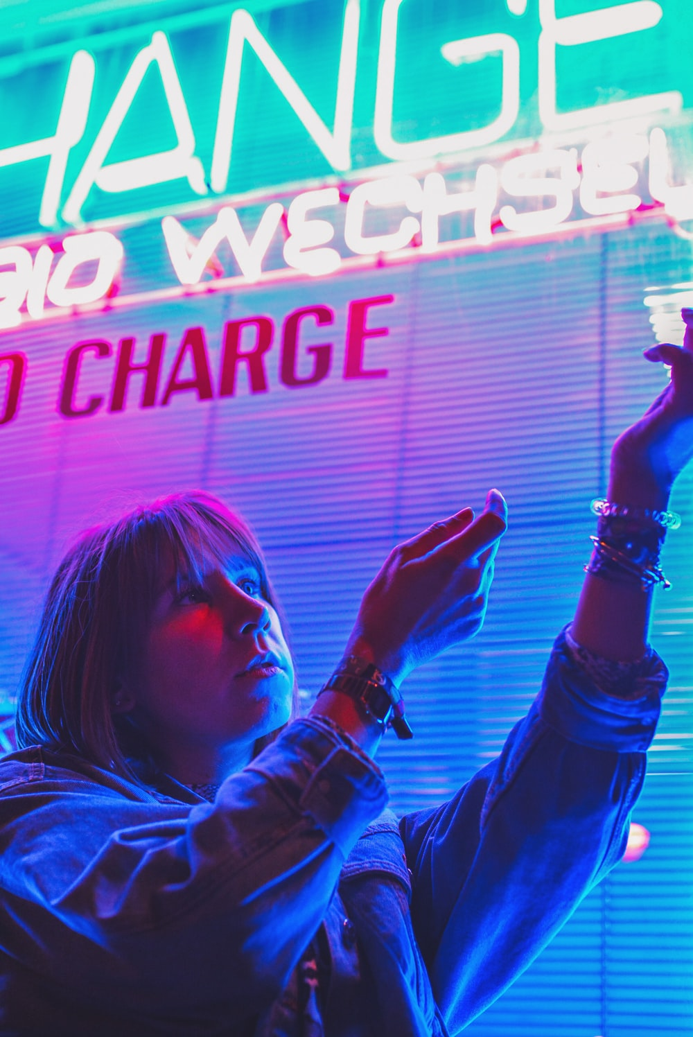 woman about to touch white and blue neon signage