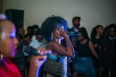 woman singing near people rwanda teams background