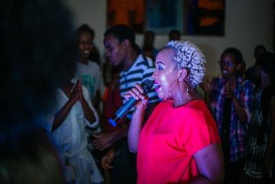 woman singing beside man dancing rwanda teams background