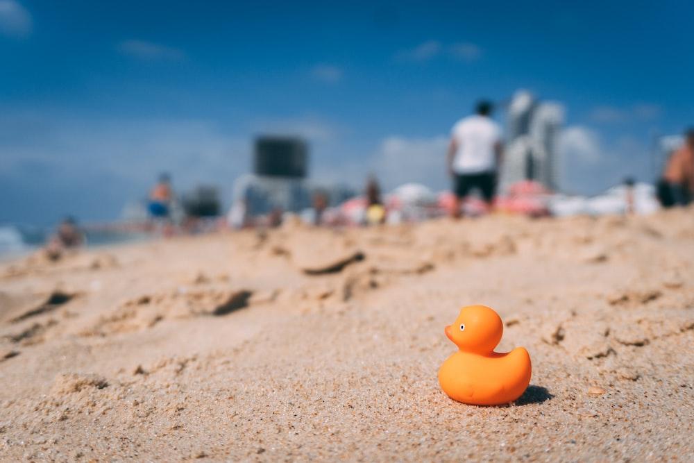 orange rubber ducky on brown sand
