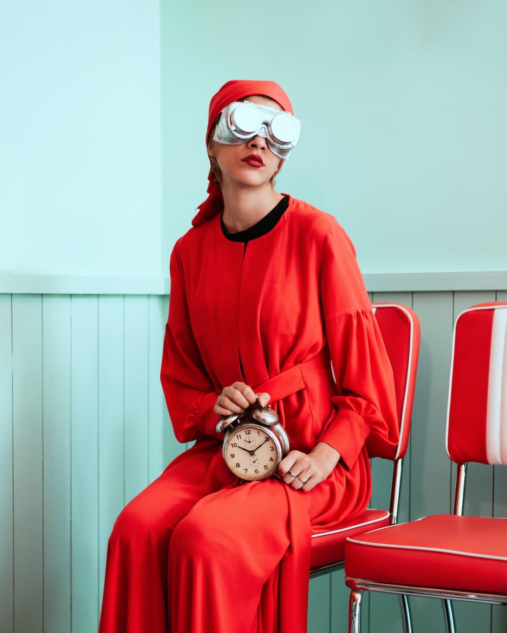 woman sitting while holding analog alarm clock