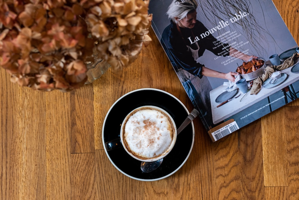 cup of cappuccino beside La Nouvelle Table book