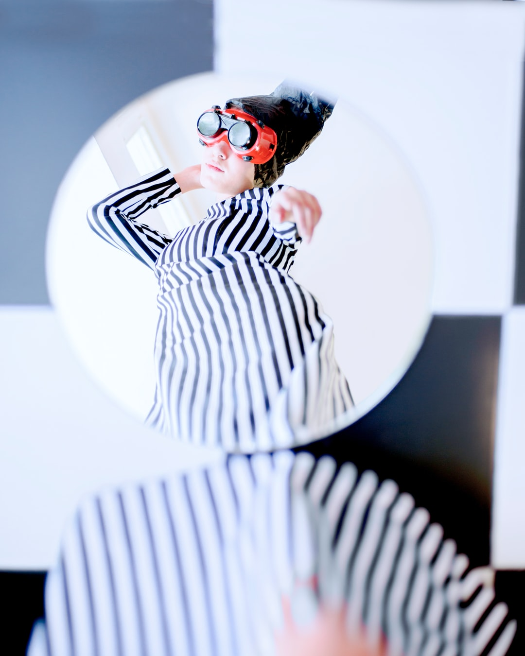 In this photo set, the locations will change along with the elements. Humans in various locations have different behavioral reflection and even use shades to hide their real behavior. The reason for the female subject in these photos is the feminine complexity inherent in them. The reason for the striped dress, however, was to create a sense of vagueness and hallucination in the observer. Mirrors, on the other hand, demonstrate the sense of reflection
