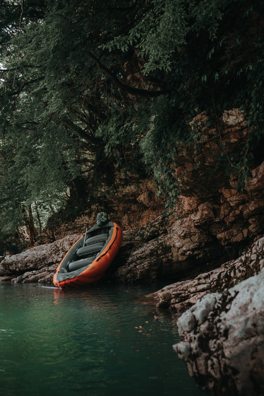 orange inflatable raft on brown stone under green tree