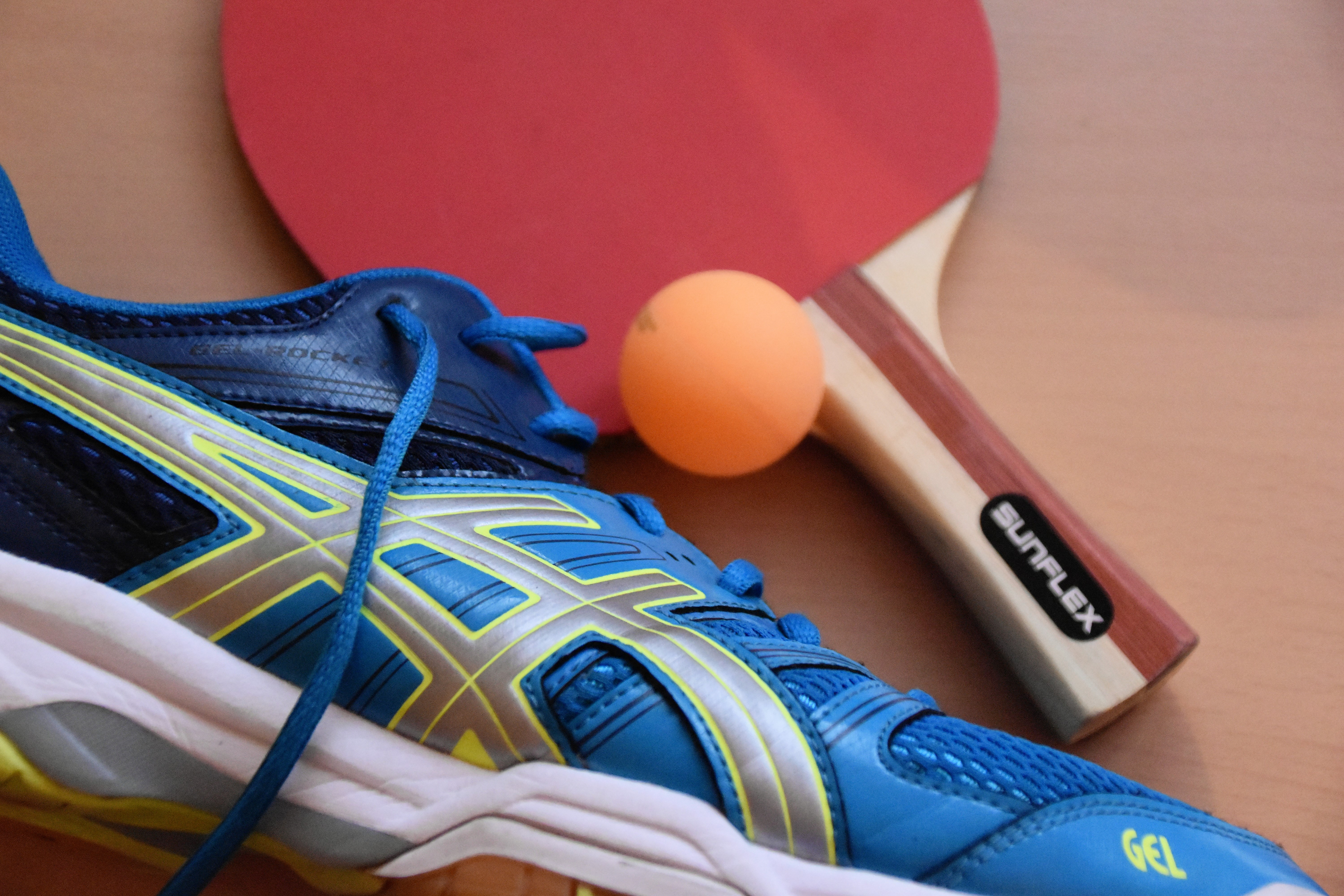 blue and black ASICS running shoes near ping pong paddle and ball