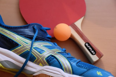 blue and black asics running shoes near ping pong paddle and ball table tennis teams background