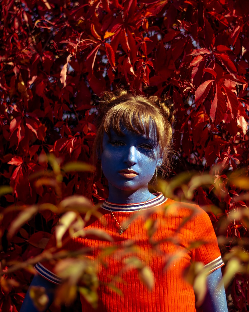 blue skinned girl wearing red crew-neck shirt surrounded by red maple leaves