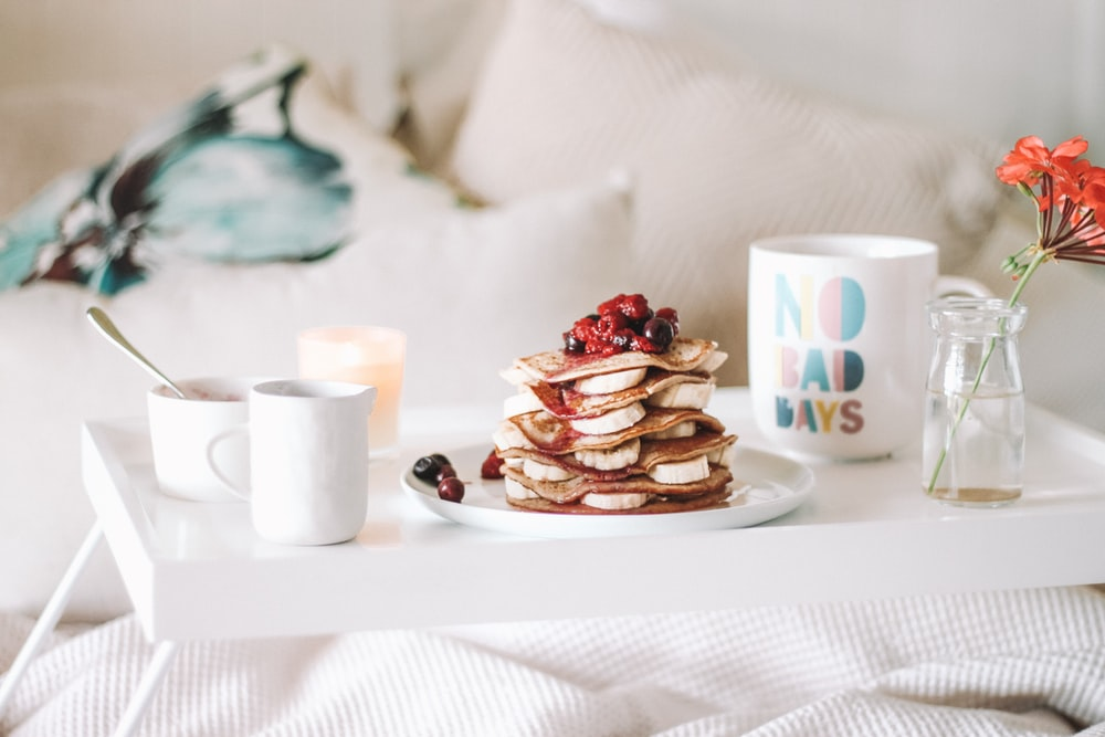 pancake with raspberries on plate beside mugs