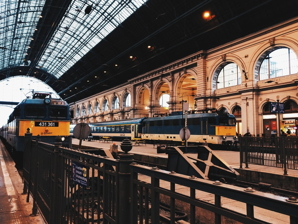 two black-and-yellow trains on train station