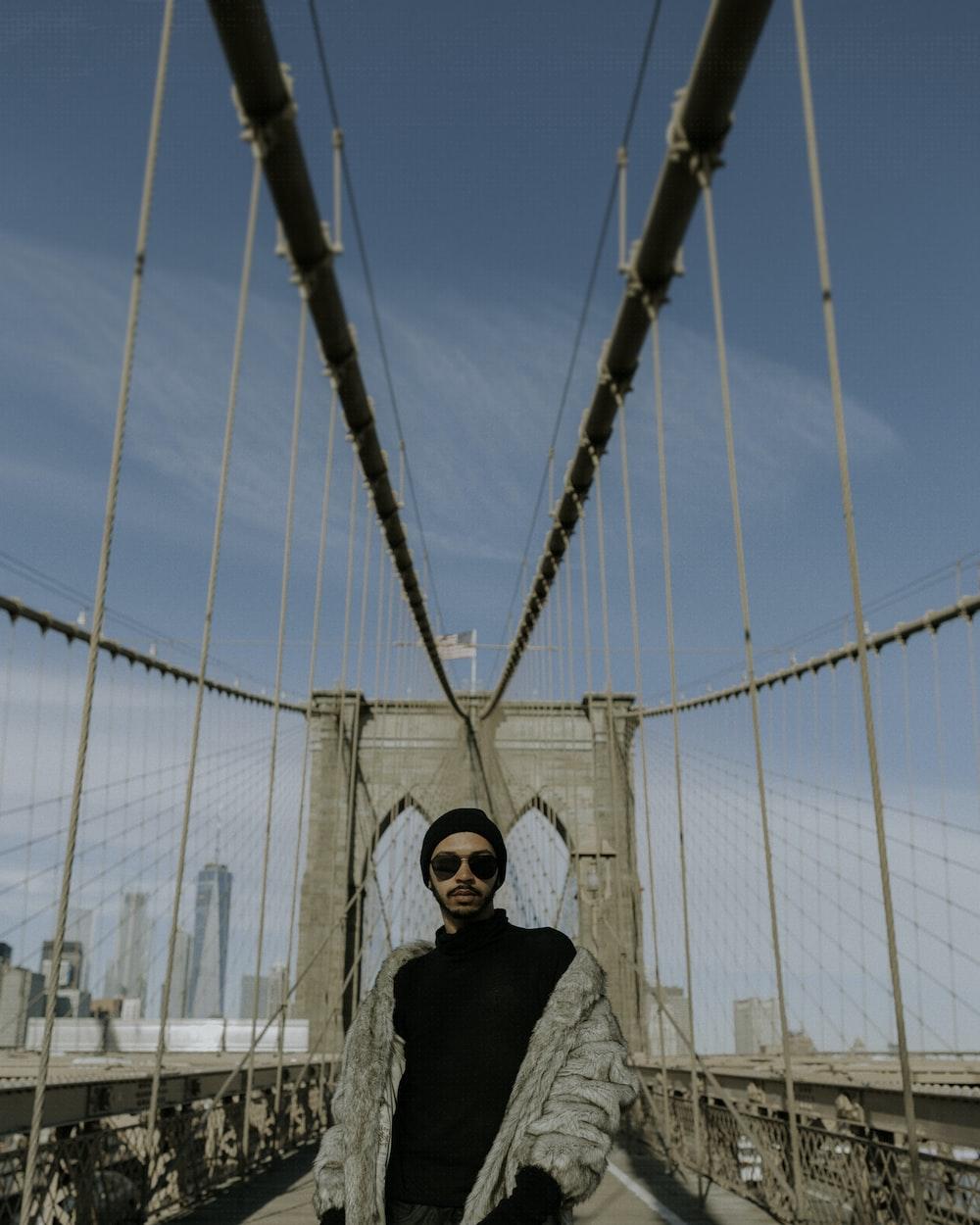 man standing between bridge during daytime