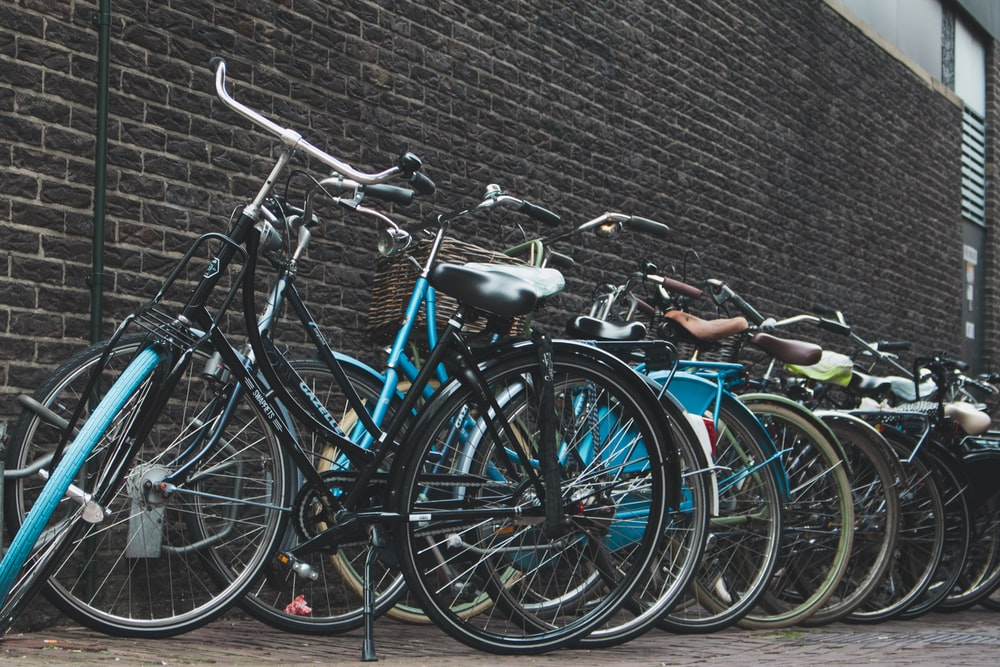assorted city bikes parked near wall
