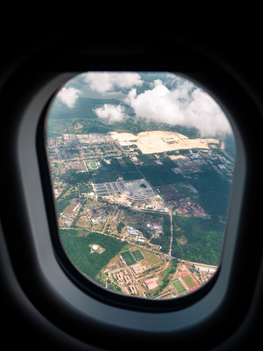 aerial photography of rural area through plane window