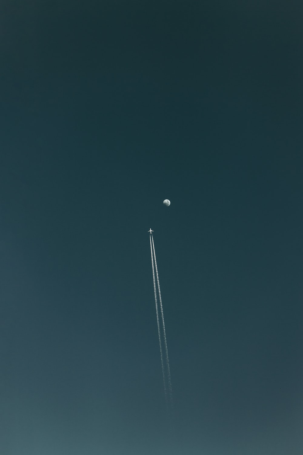 flying plane with contrail during nighttime