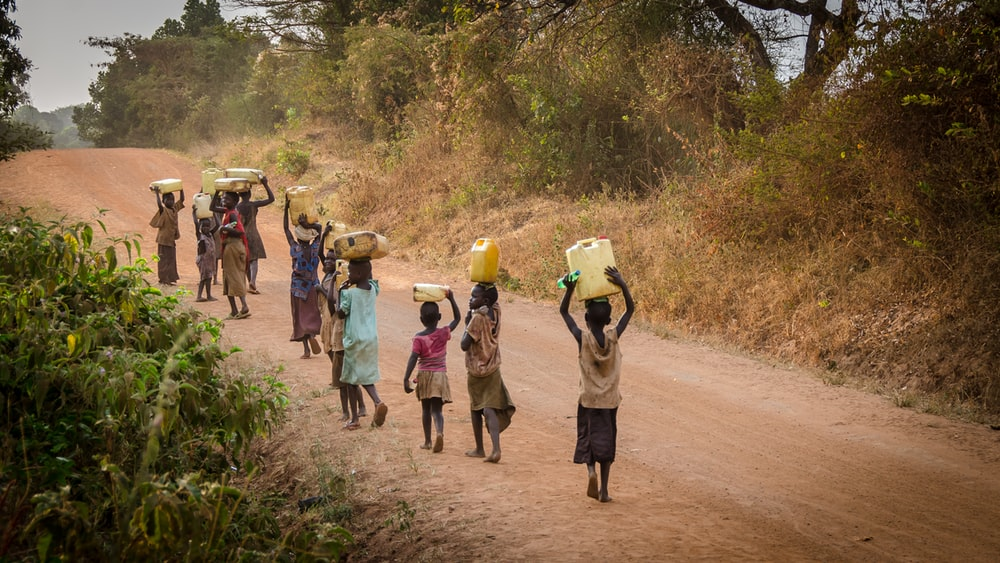 group of people walking at the road carrying containers