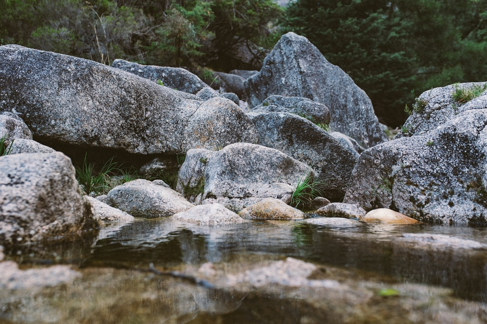 gray stone beside body of water