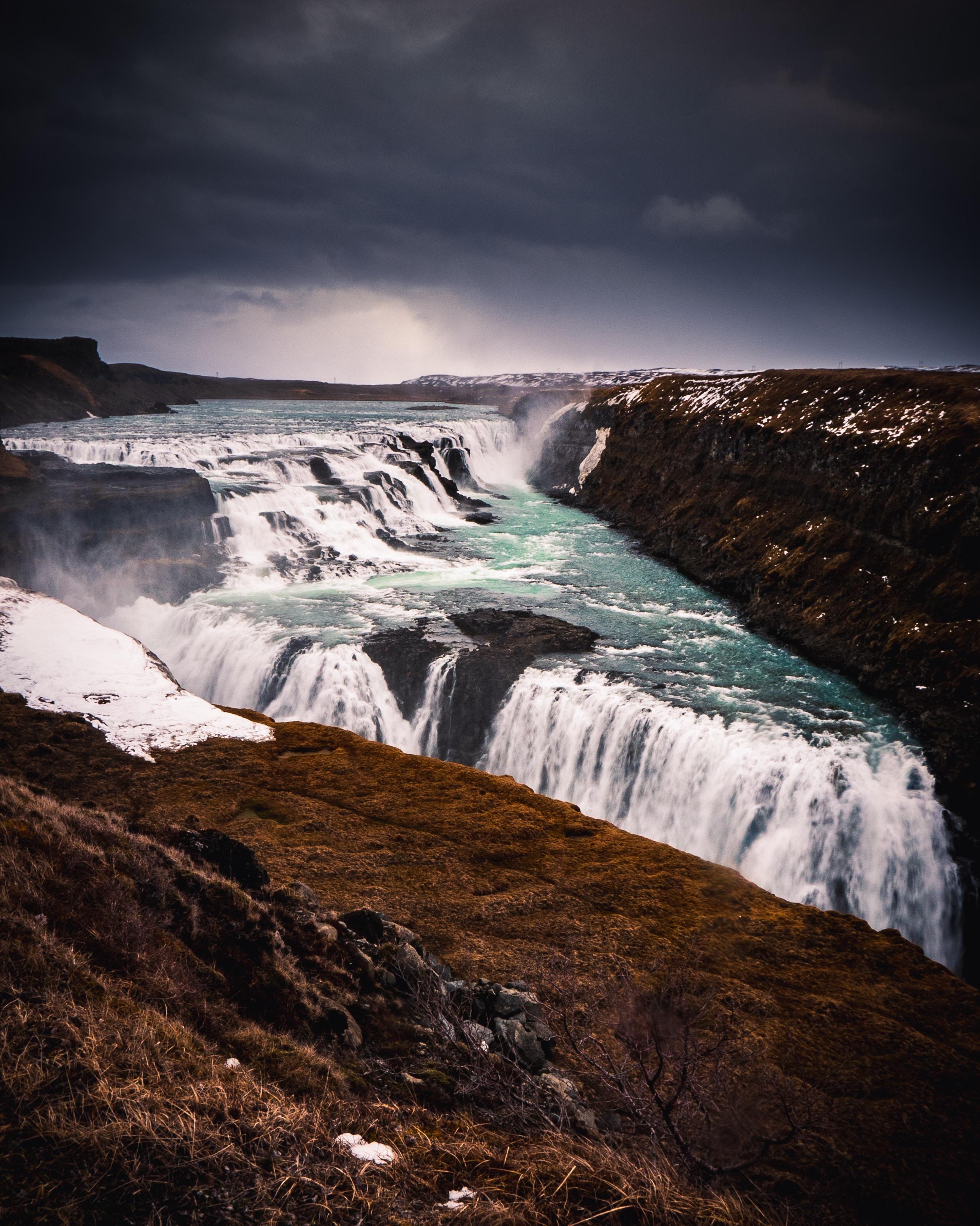 waterfalls under grey sky at daytime