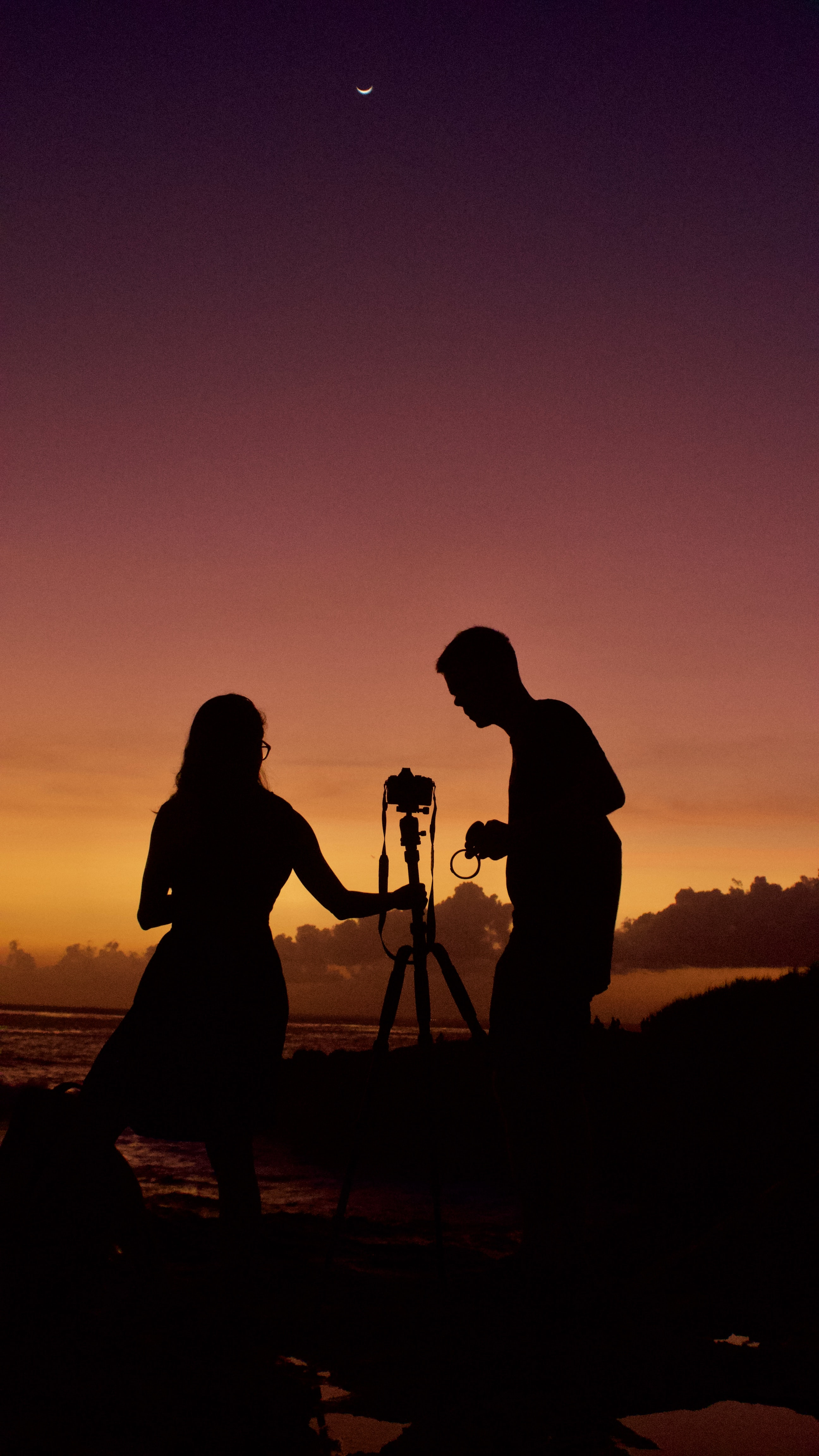 silhouette of woman and man using camera