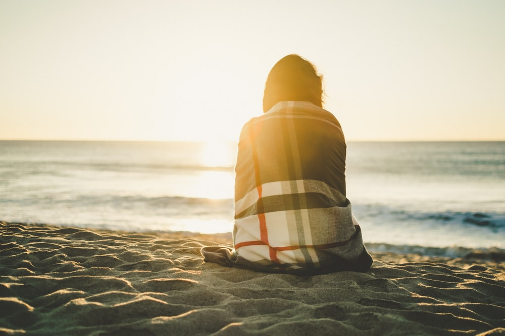 woman sitting on brown sand covered with blanket