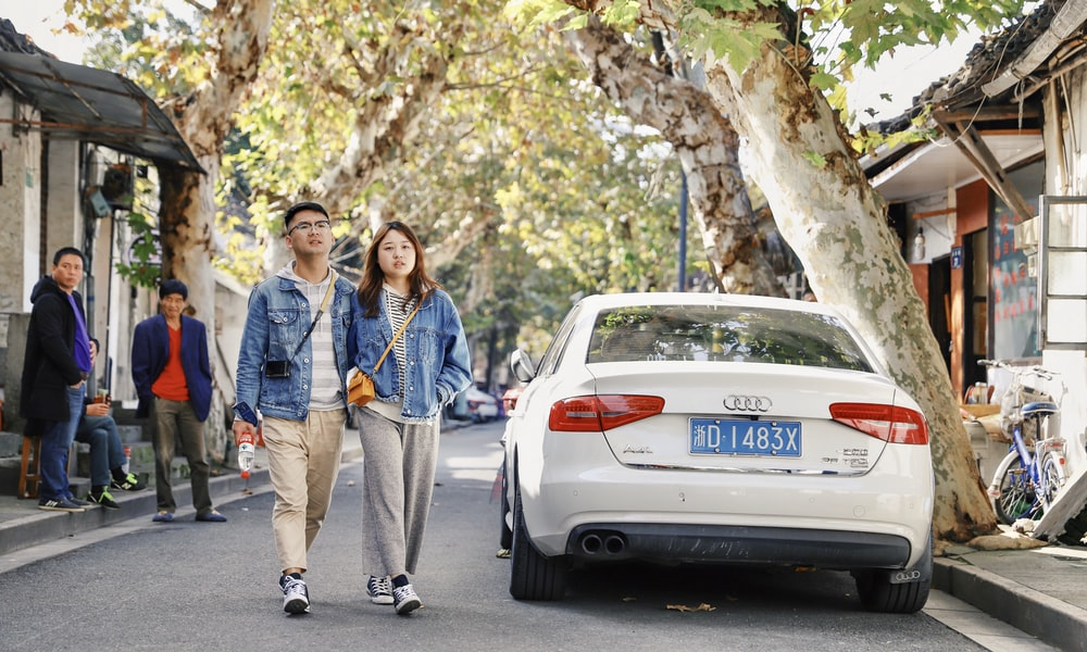 couple waking near white Audi sedan during daytime