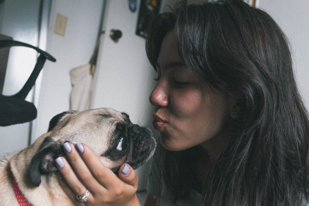 woman about to kiss dog