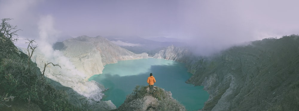 panoramic photography of person standing on cliff during daytime