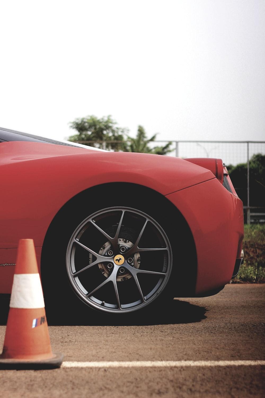 red Ferari vehicle beside traffic cone