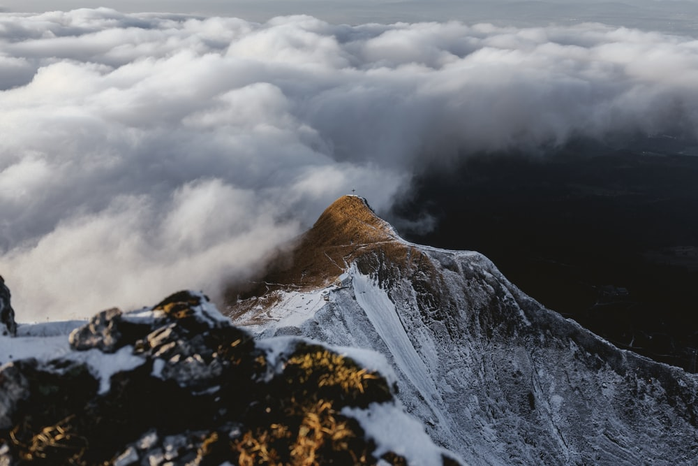 snow covered mountain under grey clouds
