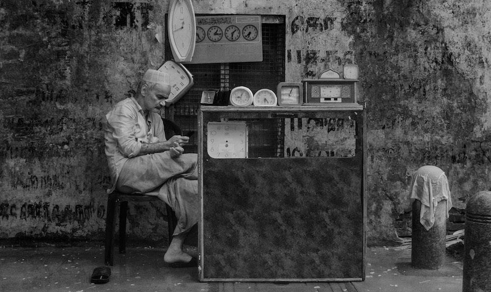 man sitting beside wall with clocks