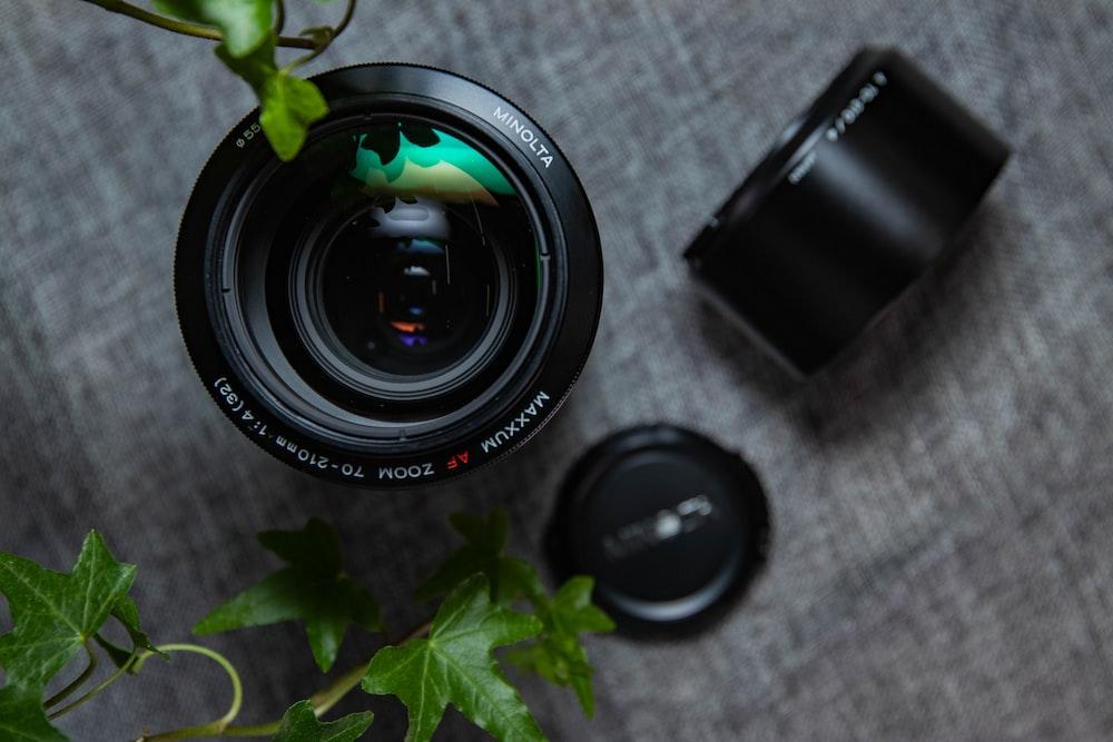 two black zoom lenses on gray linen