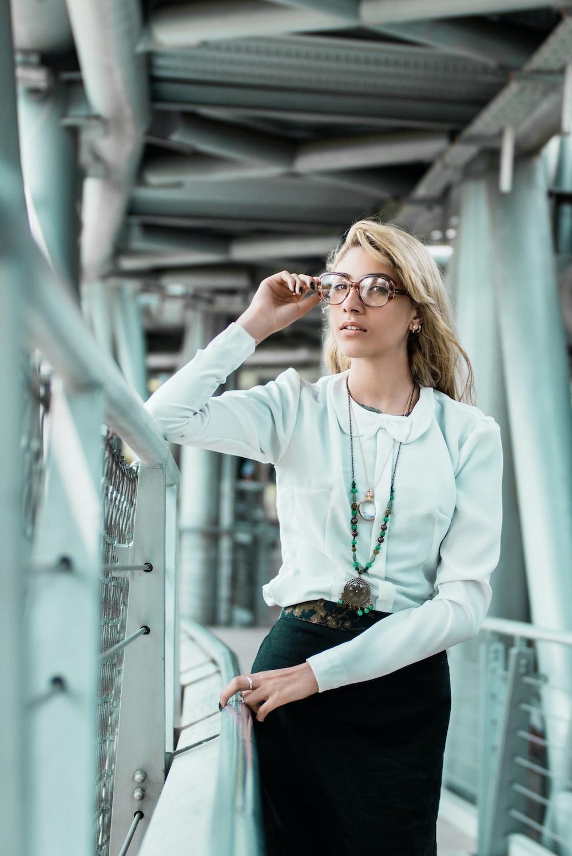 woman standing and touching eyeglasses near railings